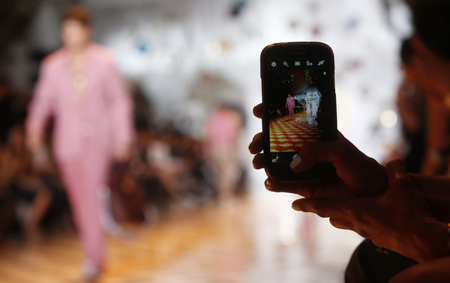 A model is pictured in a screen of a smartphone during the Versace men's Spring-Summer 2015 show, part of the Milan Fashion Week, unveiled in Milan, Italy, Saturday, June 21, 2014. (AP Photo/Luca Bruno)